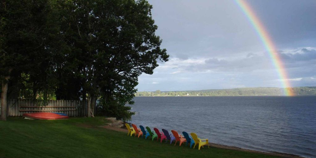 Photo of colourful chairs at lakeside with lake and rainbow in background