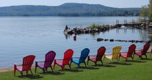 Colourful chairs lined up at the water's edge, Jocko's Beach Resort & Motel