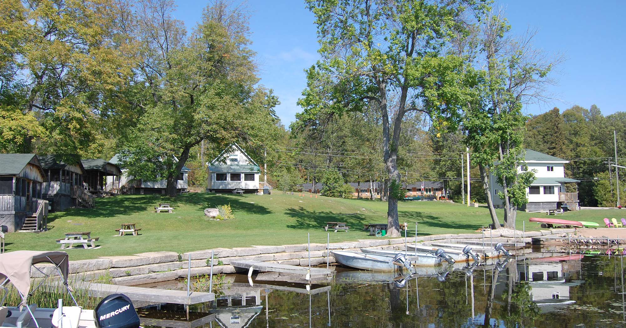 View of Jocko's Resort in summer, with fishing boats at the lake