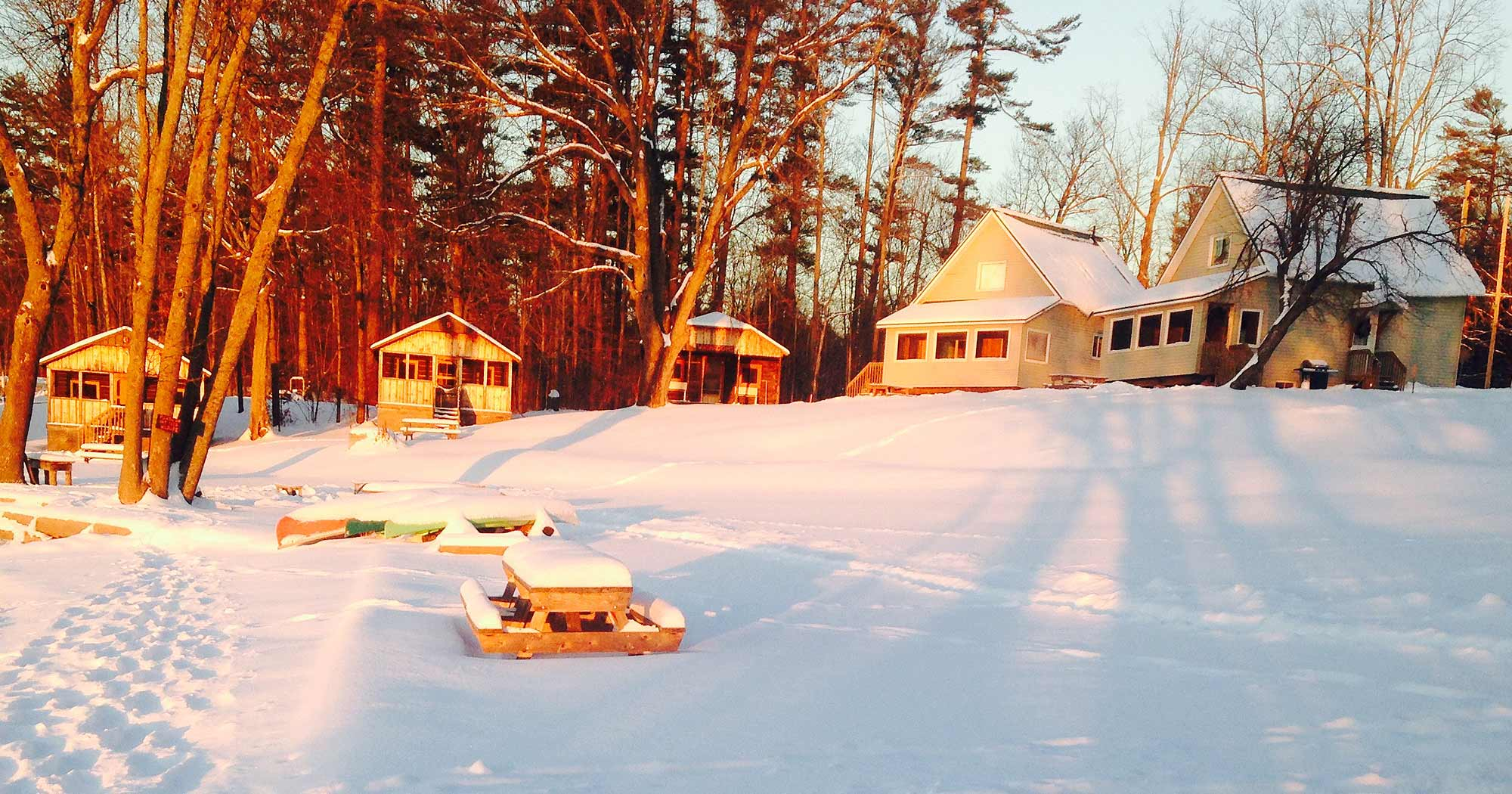 View of three log cabins and 2 chalets at Jocko's Beach Resort in winter